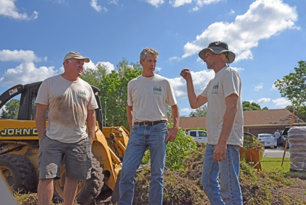 Project lead Tom Heitzman, center, with Bruce Turley at left, listen as Troy Springer describes changes he's making to the existing irrigation system.