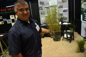 Mike Sobba, manages Martin County Farms native plant nursery for Aquatic Vegetation Control. Here, with a grass used for restoration.