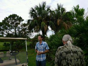 Dr. Brian Bahder on UF IFAS FLREC campus with diseased Sabal palms behind him.