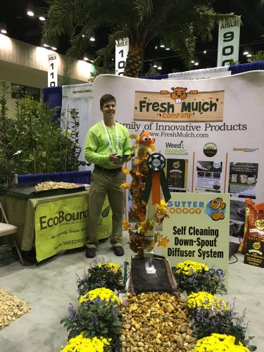 """Fresh Mulch Company, makers of Weed Recede biodegradable mulch bags, Gutter Guppy & Guppy Tails and other ecofriendly products, on display. Standing here is owner Bob Hawkinson's son Chad, helping Dad help attendees """"think beyond plastic."""""""