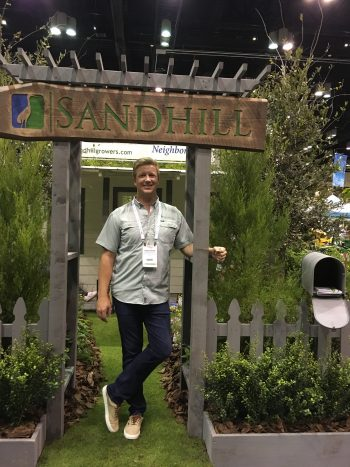 Chris Holly, Sandhill Growers & Environmental Services, stands at the entry to his booth, featuring a beautiful gray picket fence and porch surrounded by native plants.